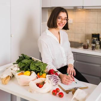 Portrait de la belle femme posant avec l'épicerie