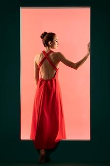 Portrait de belle femme posant avec une robe rouge fluide