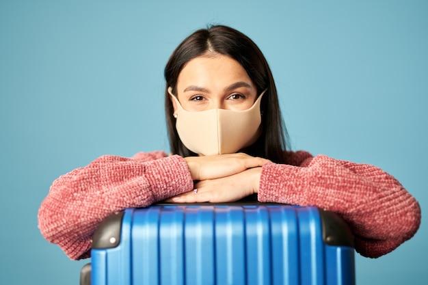 Portrait d'une belle femme posant avec une valise et portant un masque facial, isolée sur fond bleu. espace de copie. concept de voyage, coronavirus