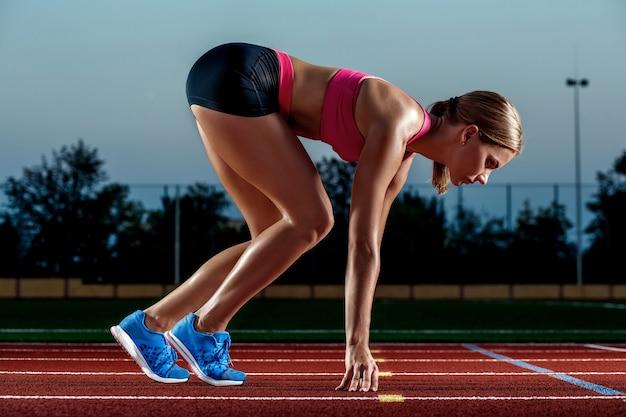 Portrait de belle femme prête à commencer à courir