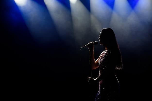 Portrait de la belle femme qui chante sur fond sombre