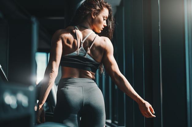 Portrait de la belle femme de race blanche bodybuilder posant dans la salle de gym avec le dos tourné. croyez en vous.