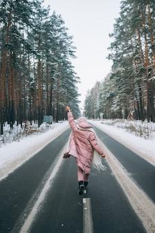 Portrait d'une belle femme de race blanche sur une route dans la forêt enneigée