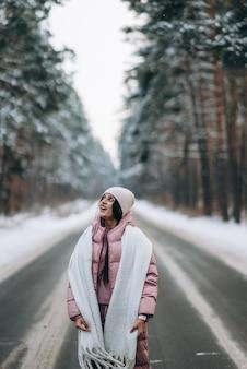 Portrait d'une belle femme de race blanche sur une route à travers la forêt enneigée