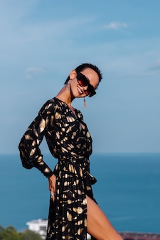 Portrait de la belle femme en robe dorée noire et lunettes de soleil au sommet de la montagne