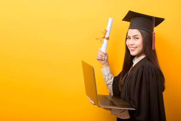 Portrait de la belle femme en robe de graduation tient un ordinateur portable sur fond jaune