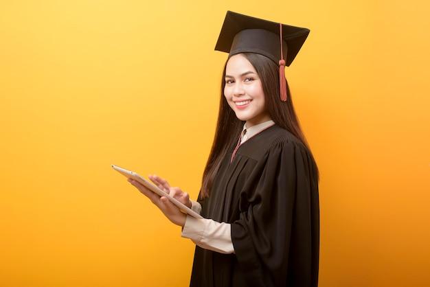 Portrait de la belle femme en robe de graduation tient la tablette sur fond jaune