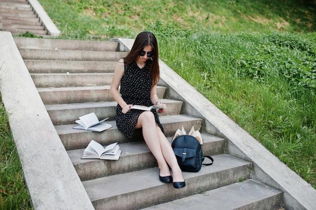 Portrait d'une belle femme en robe noire à pois et lunettes de soleil assis sur les marches avec des livres et sac à dos dans le parc.
