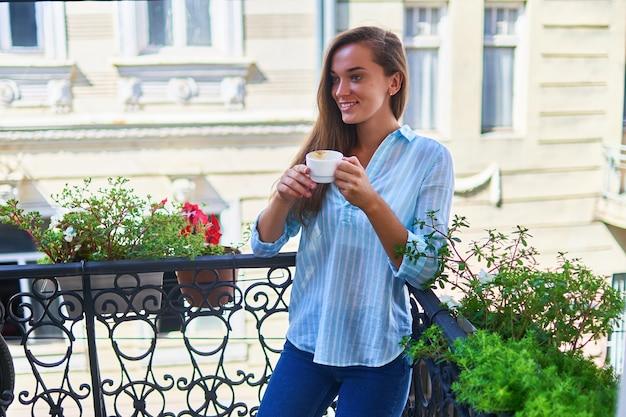 Portrait d'une belle femme romantique heureuse mignonne joyeuse souriante avec une tasse de café aromatique dans les mains le matin sur un balcon