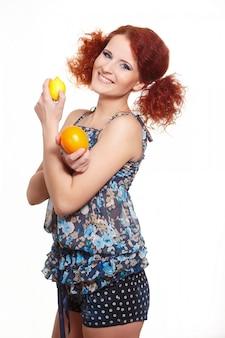 Portrait de la belle femme rousse au gingembre souriant en robe d'été isolé sur blanc avec orange et citron