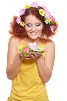 Portrait de la belle femme rousse au gingembre souriant en tissu jaune avec des fleurs colorées rose jaune dans les cheveux isolé sur blanc tenant des fleurs
