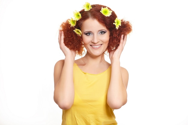 Portrait de la belle femme rousse au gingembre souriant en tissu jaune avec des fleurs jaunes dans les cheveux isolé sur blanc