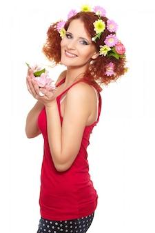Portrait de la belle femme rousse au gingembre souriant en tissu rouge avec des fleurs colorées rose jaune dans les cheveux isolé sur blanc tenant des fleurs
