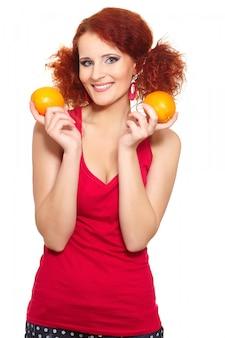 Portrait de la belle femme rousse au gingembre souriant en tissu rouge isolé sur blanc avec orange