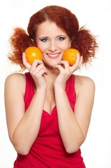 Portrait de la belle femme rousse au gingembre souriant en tissu rouge isolé sur blanc avec des oranges