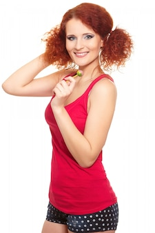 Portrait de la belle femme rousse au gingembre souriant en tissu rouge avec sweet isolated on white