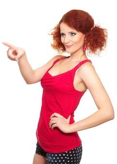 Portrait de belle femme rousse au gingembre en tissu rouge isolé sur blanc montrant quelque chose