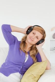 Portrait d'une belle femme rousse, écouter de la musique et profiter de l'instant tout en étant assis sur un canapé