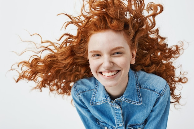 Portrait de la belle femme rousse joyeuse avec des cheveux bouclés volants souriant en riant.