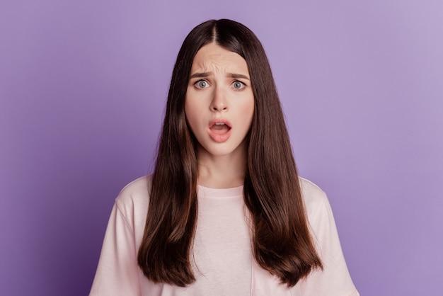 Portrait d'une belle femme sans voix bouche ouverte regarde la caméra sur le mur violet