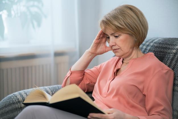 Portrait de la belle femme senior adulte intelligente lit un livre intéressant à la maison assis sur