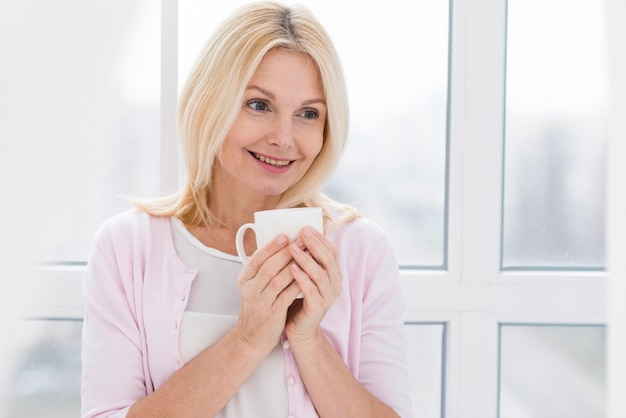 Portrait de la belle femme senior avec une tasse