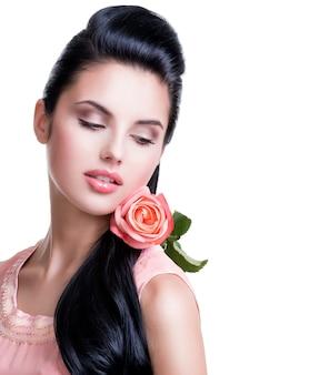 Portrait de belle femme sensuelle avec rose rose sur mur blanc.