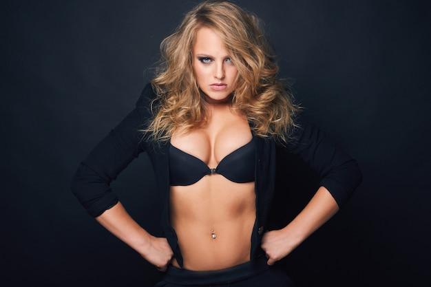 Portrait de la belle femme sexy blonde sur fond noir