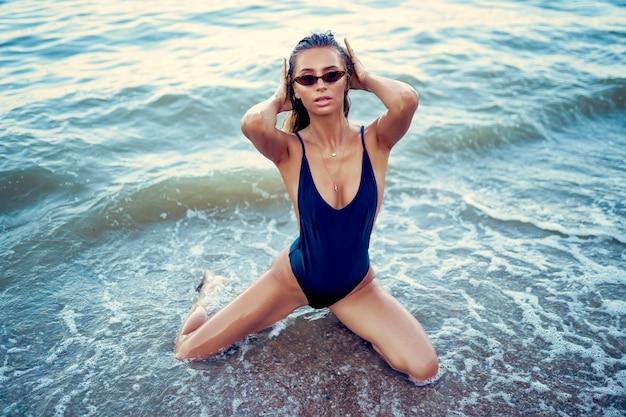 Portrait de la belle femme sexy caucasienne bronzée à lunettes de soleil