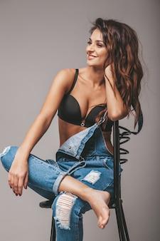 Portrait de la belle femme sexy en jeans dans l'ensemble. fille mignonne hipster attrayant, assis sur une chaise. modèle, poser, studio