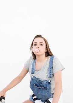 Portrait d'une belle femme soufflant du bubble-gum sur fond blanc