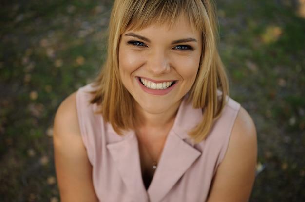 Portrait d'une belle femme souriante assise sur l'herbe verte dans le parc