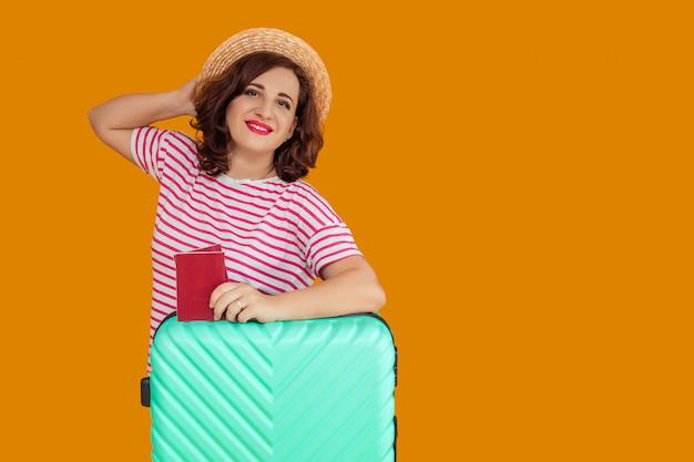 Portrait d'une belle femme souriante aux cheveux bouclés noirs dans un chapeau de plaisancier. une femme est titulaire d'un passeport dans ses mains et s'appuie sur une valise. en attente de voyage