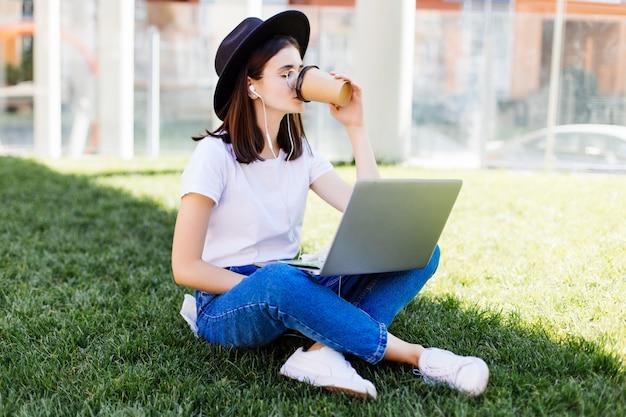 Portrait de la belle femme souriante boire du café assis sur l'herbe verte dans le parc avec les jambes croisées pendant la journée d'été tout en utilisant un ordinateur portable