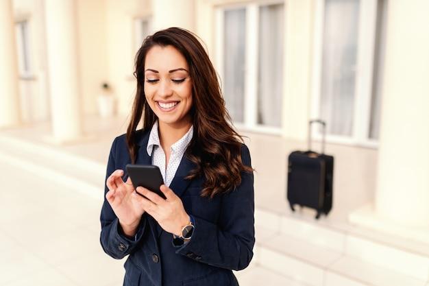 Portrait de la belle femme souriante caucasienne à l'aide d'un téléphone intelligent pour appeler le taxi. en arrière-plan des bagages. concept de voyage d'affaires.