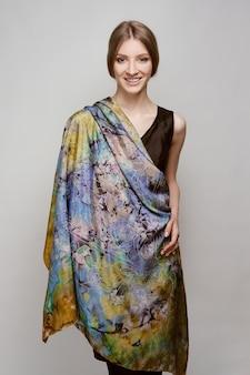 Portrait de la belle femme souriante avec châle en soie colorée