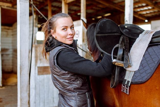 Portrait belle femme souriante cheveux longs à côté de son cheval dans une étable