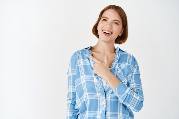 Portrait de belle femme souriante sur l'espace de copie. fille pointant vers la gauche, debout dans une chemise à carreaux décontractée sur un mur blanc