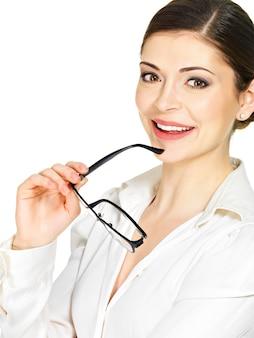 Portrait d'une belle femme souriante heureuse avec des lunettes en mains- isolé sur fond blanc
