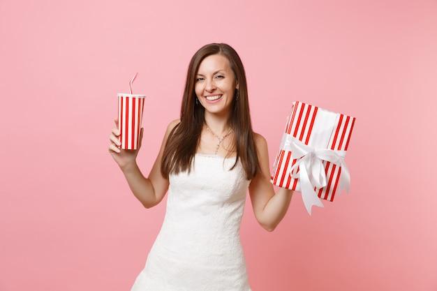 Portrait d'une belle femme souriante en robe blanche tenant une boîte rouge avec un cadeau, présente une tasse en plastique avec du cola ou du soda
