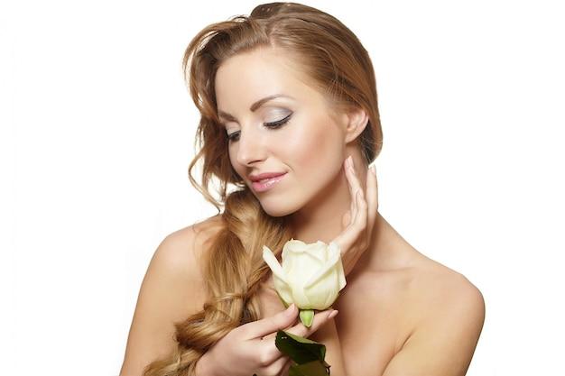 Portrait de belle femme souriante sensuelle avec rose blanche sur blanc