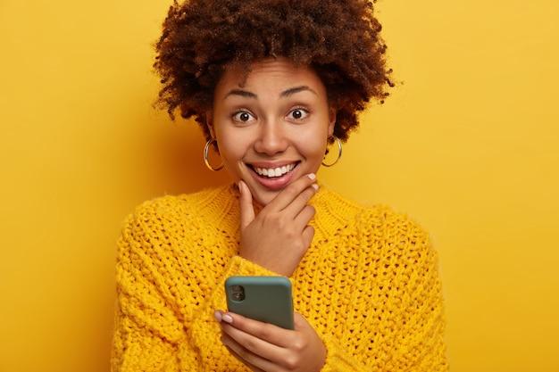 Portrait de belle femme souriante touche le menton, sourit largement, utilise un téléphone portable, porte un pull jaune, des modèles à l'intérieur.