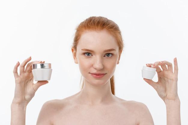 Portrait de la belle femme souriante tout en prenant de la crème pour le visage isolé sur blanc