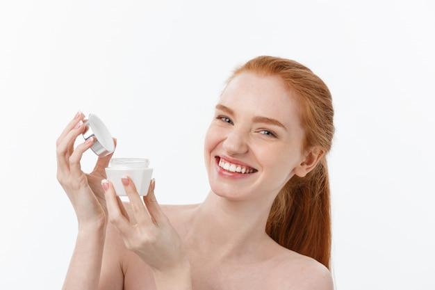 Portrait de la belle femme souriante tout en prenant de la crème pour le visage isolé sur fond blanc avec espace de copie.