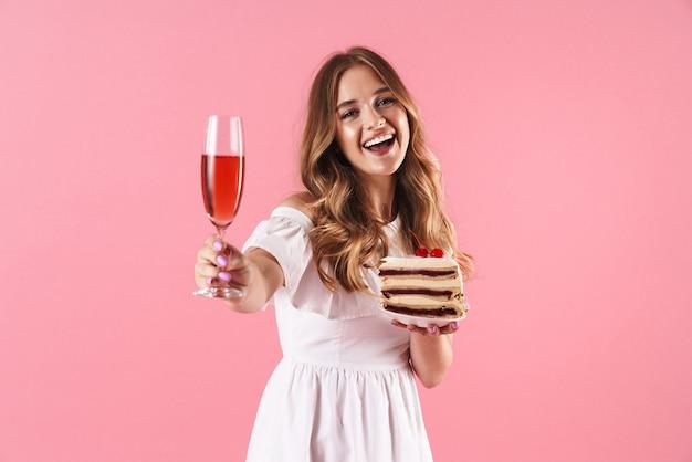 Portrait d'une belle femme souriante vêtue d'une robe blanche tenant un morceau de gâteau et un verre de vin isolé sur un mur rose