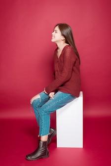 Portrait de belle femme en studio sur le rouge