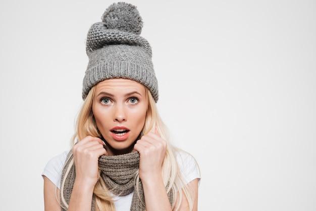 Portrait d'une belle femme surprise au chapeau d'hiver