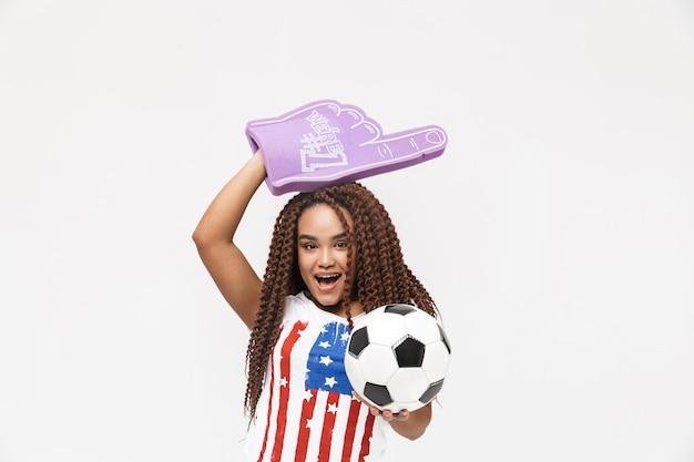 Portrait d'une belle femme tenant un gant de fan numéro un et un ballon de football en se tenant debout isolé contre un mur blanc
