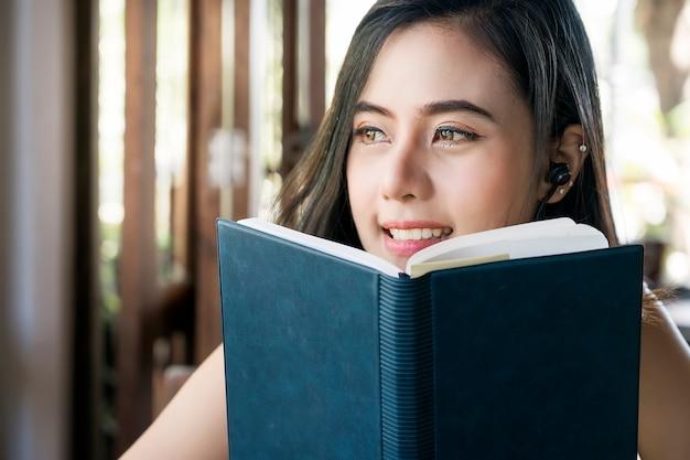 Portrait de belle femme tenant un livre et regardant par la fenêtre.