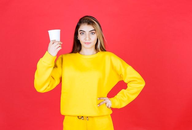 Portrait de belle femme en tenue jaune posant avec une tasse de thé